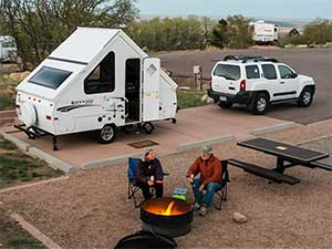 a frame popup camper with couple in arkansas campground