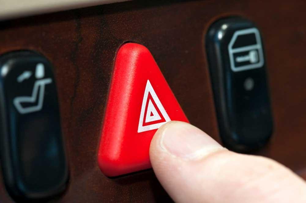 person turning on hazard flashers during roadside emergency in arkansas